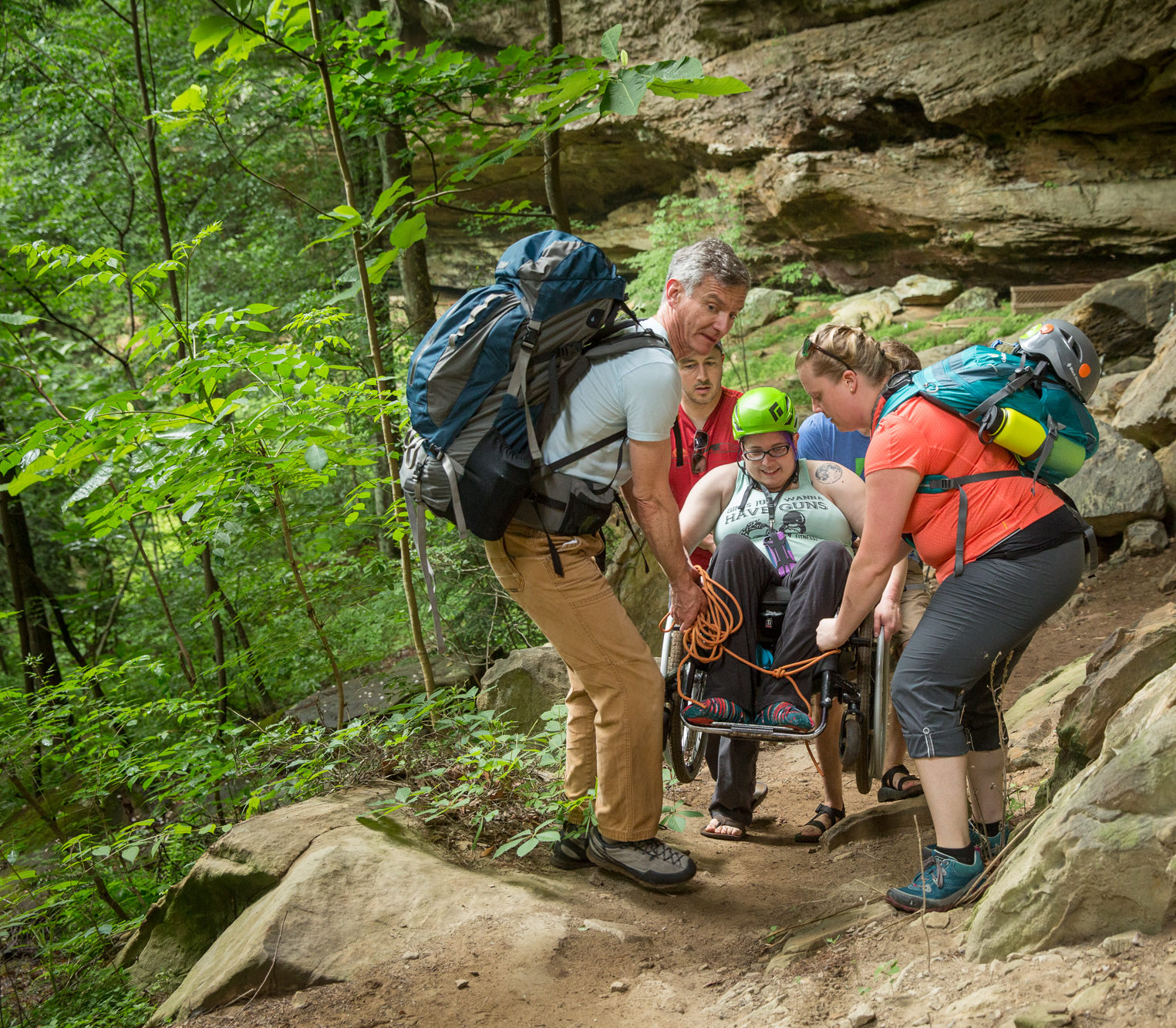 Volunteers helping climber in their wheelchair to the crag on Red River Gorge Trip in 2018