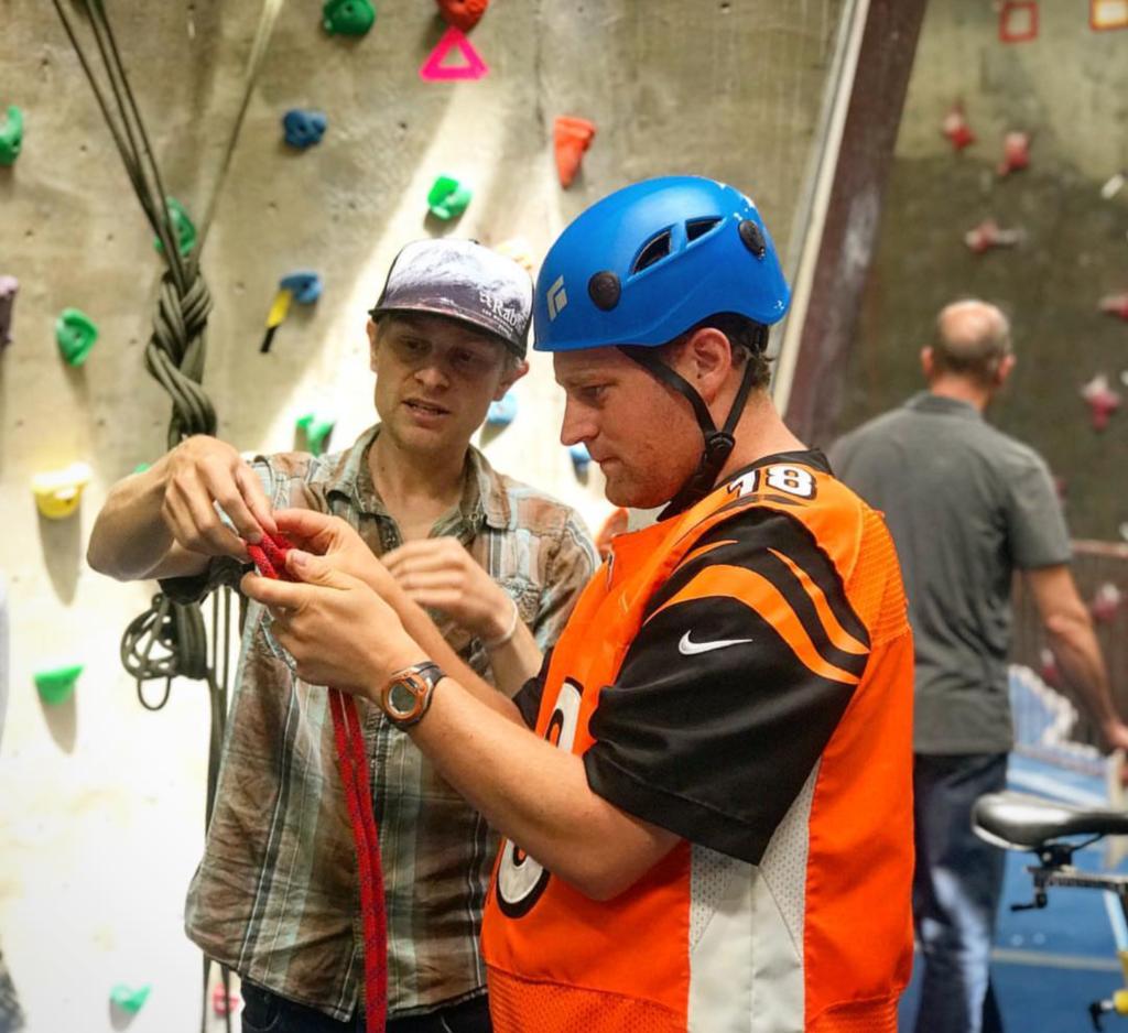 Ryan Pedersen helping clikmbers for Imagine! Boulder at BRC